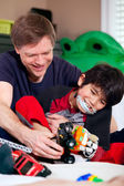 Handsome father playing cars with disabled son — 图库照片