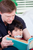 Father reading book to disabled little son — 图库照片