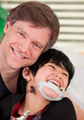 Smiling father holding disabled son — 图库照片