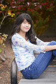 Young preteen girl sitting on park bench outdoors — Stock Photo