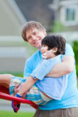 Father helping disabled seven year old son play at playground — Stock Photo