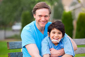 Handsome father holding smiling disabled son outdoors — Stock Photo
