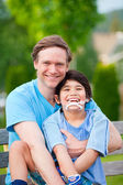 Handsome father holding smiling disabled son outdoors — 图库照片