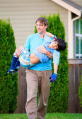 Father carrying disabled son outdoors — Stock Photo