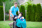 Father racing around park with disabled son in wheelchair — Stock Photo