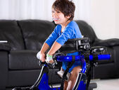 Disabled biracial boy in medical walker. Living room setting. — Stok fotoğraf