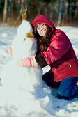 Young girl in red jacket playing outdoors in snow — Stock Photo