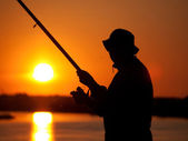 Fisherman on sunset — Stock Photo