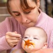 Mum spoon-feeds the child — Stock Photo