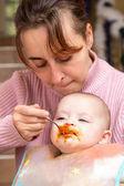 Mum spoon-feeds the child — Stock Photo