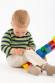Little cute boy playing with building blocks. Isolated on white. — Stockfoto
