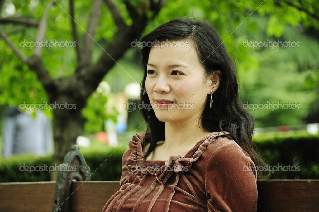 Picture of a smiling lady siting at bench at park. — Stock Photo #12838114