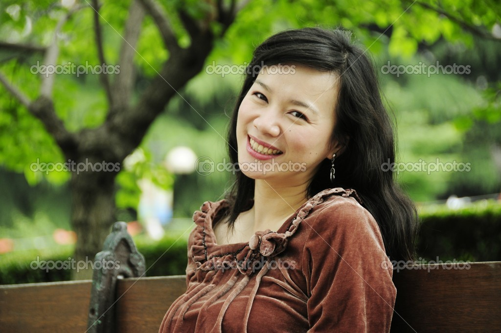 Picture of a smiling lady siting at bench at park. — Stock Photo #12838215