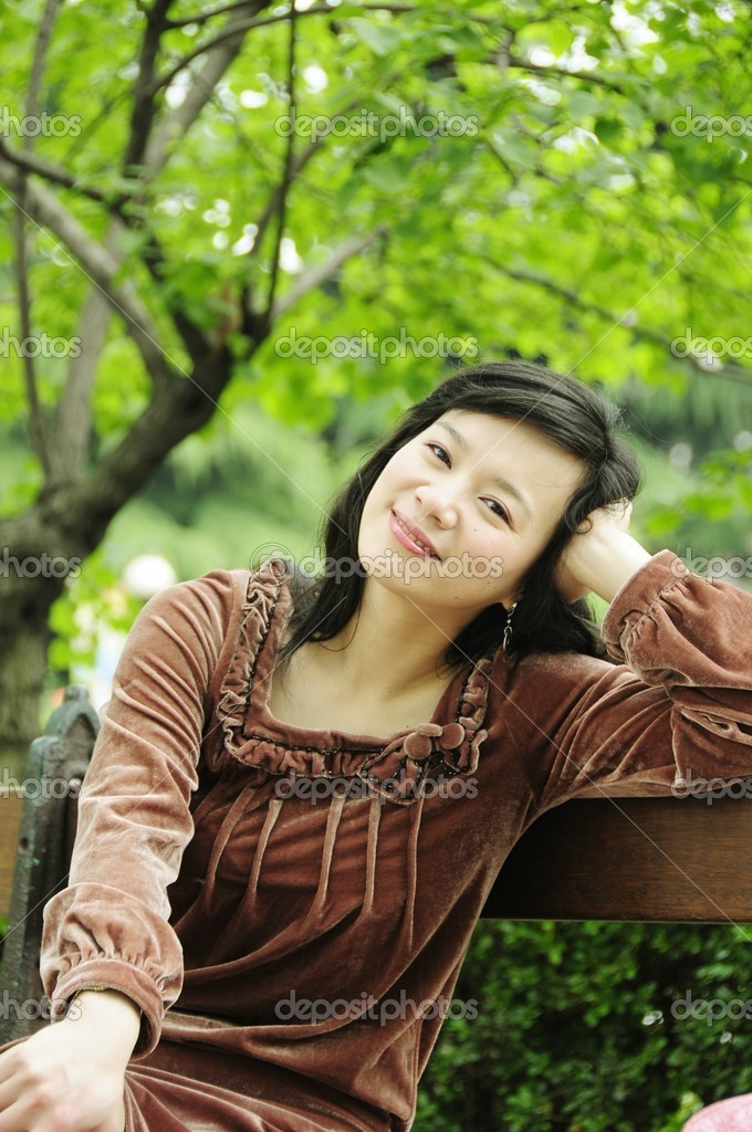 Picture of a smiling lady siting at bench at park. — Stock Photo #12838237
