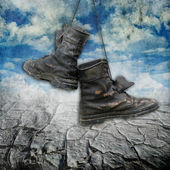 Old and dirty military boots over grunge background with clouds and drought land — Stock Photo