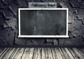 Grunge interior with blackboard on cracked wall — Stock Photo