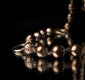 Golden necklace over black — Stock Photo