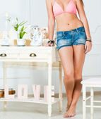 Model wearing pink bra and denim shorts posing against white table — Stock Photo