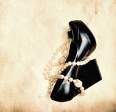 Shoe and pearl necklace over grunge background — Stock Photo