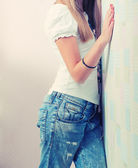 Blonde girl standing near wall — Stock Photo