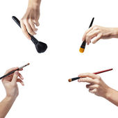 Isolated female hands with a brushes for makeup — Stock Photo