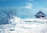 The old wooden roof covered with snow and blue sky — Stock Photo