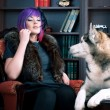 Pink hair lady and dog in a library  — Stock Photo