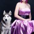Young woman in pink silk dress with dog — Stock Photo