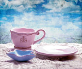Pink cup, saucer and starfish shaped bowl on table over grunge — Stock Photo