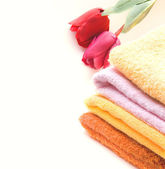 Stack of colorfull towels and tulips isolated — Stock Photo