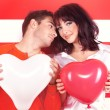Charming love couple with heart-shaped balloon — Stock Photo