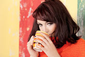 Beautiful young woman in casual wear with cup — Stock Photo