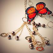 Gyllene pärlor med fjäril — Stockfoto