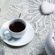 White coffee cup on wooden table with crochet doily — Stock Photo