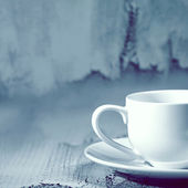 Cup of coffee on old wall background — Stock Photo