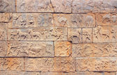 Wall with a carved relief: scenes of hunting and life. India — Stock Photo