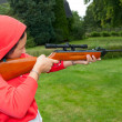 Young woman shooting with airgun - Stock Photo