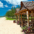 Tropical beach scenery with huts - Stock Photo