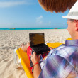 Man with laptop relaxing on the deckchair — Stock Photo