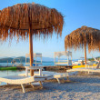 Sunbeds with parasols at sunset on Crete - Stock Photo