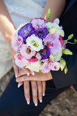 Hands of bride and groom with bouquet — Stock Photo