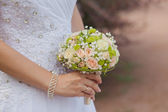 Wedding bouquet of roses in the hands of the bride — Stock Photo