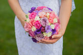 Wedding bouquet of roses and eustoma in the hands of the bride — Stock Photo