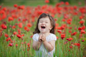 Very happy child girl in poppy field — Stock Photo