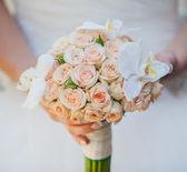 Beautiful wedding bouquet in hands of the bride — Stock Photo