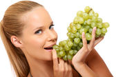 Closeup portrait of a healthy woman bites in grape — Stock Photo