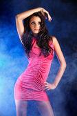 Fashion model portrait in dark, smoky studio — Stock Photo