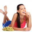 Happy teenager eating grapes isolated on white — Stock Photo