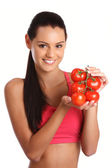 Young brunette woman posing with tomatoes — Stock Photo