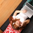 Young Redhead Girl surfing on the Sofa — Stock Photo #13142412